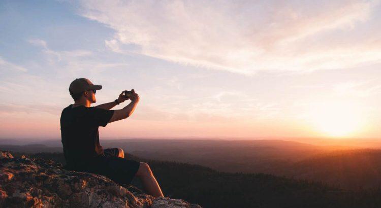 Ein Mann sitzt auf dem Gipfel eines Berges und macht ein Foto