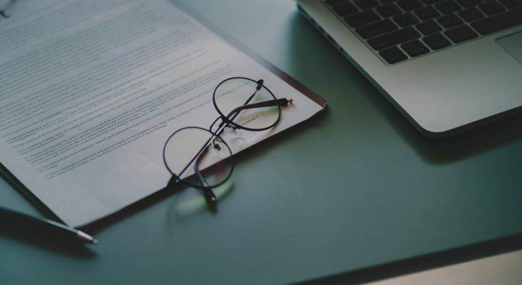 EIne Brille liegt auf einem Dokument neben einem Laptop