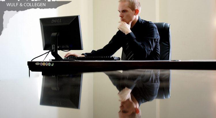Ein Mitarbeiter sitzt grübelnd vor seinem Bildschirm