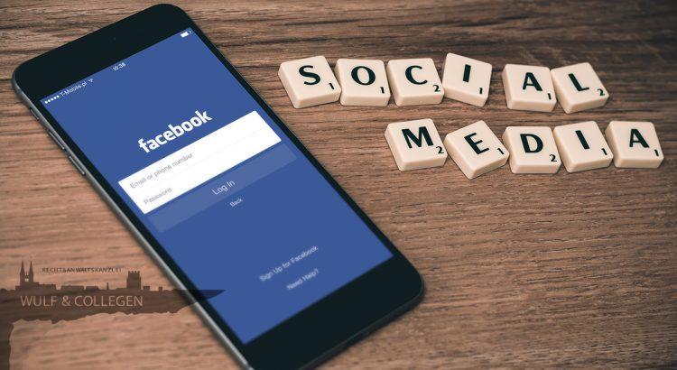 """Ein Handy mit dem Facebook-Login, wo daneben Scrabble-Steine liegen, auf denen """"Social Media"""" zu lesen ist"""