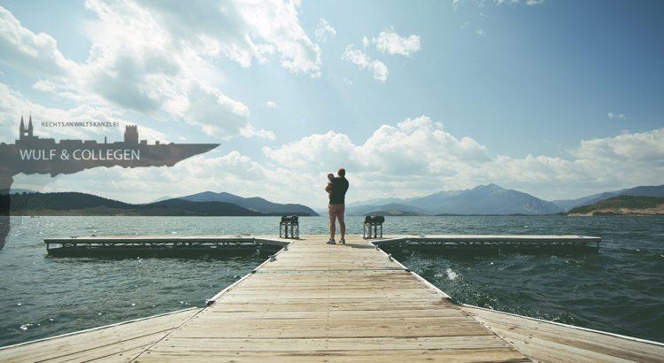EIn Vater steht mit einem Kind auf dem Arm auf einem Bootssteg